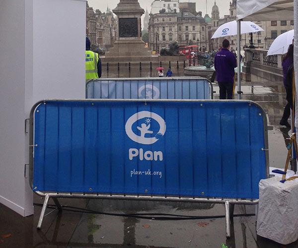 Plan UK logo on a blue barrier scrim
